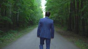 Homem de negócios novo considerável que anda ao longo da estrada na floresta, vista para trás vídeos de arquivo