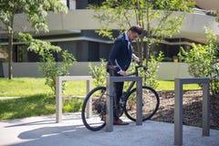 Homem de negócios novo considerável que estaciona sua bicicleta no trabalho imagem de stock