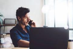 Homem de negócios novo considerável que trabalha no lugar de trabalho ensolarado no portátil Homem elegante que usa o smartphone  fotografia de stock royalty free