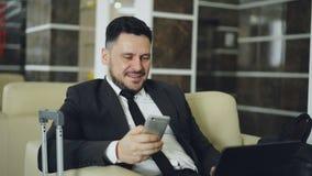 Homem de negócios novo considerável que usa o smarphone e o laptop ao trabalhar na entrada confortável do hotel com bagagem filme