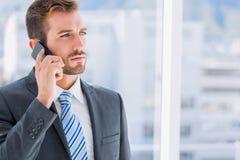 Homem de negócios novo considerável que usa o telefone celular fotografia de stock royalty free
