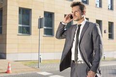 Homem de negócios novo considerável que usa o telefone celular fora imagens de stock