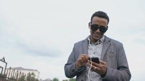 Homem de negócios novo da raça misturada que escuta a música em seu smartphone fora filme