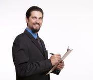 Homem de negócios novo de sorriso com uma prancheta que faz anotações Fotos de Stock Royalty Free