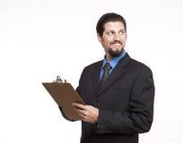 Homem de negócios novo de sorriso com uma prancheta que olha afastado Fotos de Stock