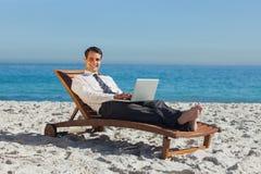 Homem de negócios novo de sorriso que encontra-se em uma cadeira de plataforma com seu portátil Fotografia de Stock