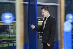 Homem de negócios novo de sorriso que está na frente de um ATM e de olhar seu telefone Fotografia de Stock Royalty Free