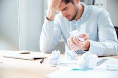 Homem de negócios novo desesperado cansado que trabalha e papel de amarrotamento Fotos de Stock