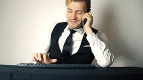 Homem de negócios novo do escritório que trabalha no computador de secretária Homem de negócio de sorriso que datilografa no tecl vídeos de arquivo
