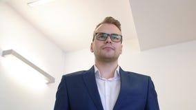 Homem de negócios novo do retrato nos monóculos e terno azul no fundo branco do escritório vídeos de arquivo