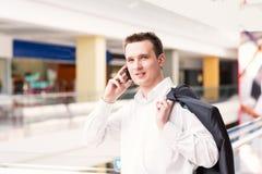 Homem de negócios novo e bem sucedido considerável que fala em seu telemóvel Imagens de Stock Royalty Free