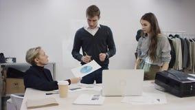 Homem de negócios novo e duas mulheres de negócios que discutem seu projeto da roupa e que examinam documentos video estoque