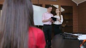 Homem de negócios novo e mulher de negócios que dão uma apresentação no escritório moderno