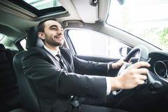 Homem de negócios novo em seu carro Motorista do carro luxuty Carro considerável da movimentação do homem imagens de stock