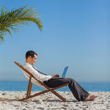 Homem de negócios novo em sua cadeira de praia usando seu portátil Fotografia de Stock Royalty Free