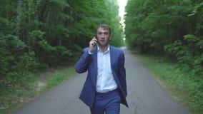 Homem de negócios novo em um terno azul que anda ao longo da estrada e que fala no telefone filme