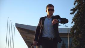 Homem de negócios novo em um terno preto formal que olha seu relógio e que vai rapidamente com sua bagagem Homem considerável den video estoque