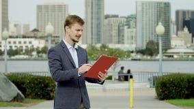 Homem de negócios novo em uma rua com uma tabela plana video estoque