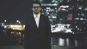 Homem de negócios novo em vidros Arquitetura da cidade no fundo da noite Imagem de Stock Royalty Free