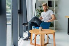 Homem de negócios novo farpado que trabalha no escritório moderno Equipe o t-shirt branco vestindo e notas da fatura nos originai Fotografia de Stock Royalty Free