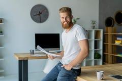 Homem de negócios novo farpado que trabalha no escritório moderno Equipe o t-shirt branco vestindo e notas da fatura nos originai Imagens de Stock Royalty Free