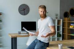 Homem de negócios novo farpado que trabalha no escritório moderno Equipe o t-shirt branco vestindo e notas da fatura nos originai Imagem de Stock Royalty Free