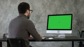 Homem de negócios novo farpado que woking no computador Exposição verde do modelo da tela video estoque