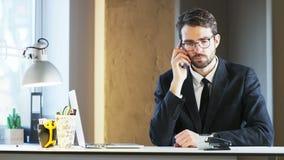 Homem de negócios novo Feeling Distracted While que fala no telefone filme