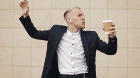 Homem de negócios novo feliz com café que escuta a música nos fones de ouvido no smartphone e na dança engraçada perto do escritó filme