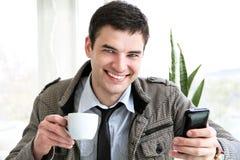 Homem de negócios novo feliz que usa o telefone móvel fotografia de stock royalty free