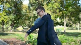 Homem de negócios novo fora no parque usando o smartphone do telefone celular, pondo o blazer do revestimento do terno e andando  video estoque