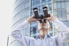 Homem de negócios novo Looking Through Binoculars Fotos de Stock Royalty Free