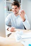 Homem de negócios novo louco irritado que usa o computador no local de trabalho Imagem de Stock Royalty Free