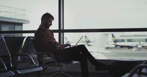 Homem de negócios novo no aeroporto que senta-se na cadeira e que espera seu embarque que trabalhou em seu portátil muito filme