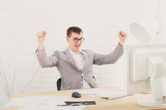 Homem de negócios novo no escritório com computador Fotografia de Stock