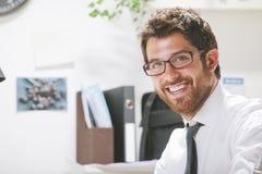 Homem de negócios novo no escritório que olha a câmera. Fotos de Stock Royalty Free