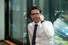 Homem de negócios novo no telefone Fotografia de Stock Royalty Free