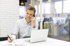 Homem de negócios novo no telefone celular no escritório Foto de Stock Royalty Free