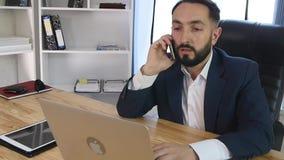Homem de negócios novo no telefone no escritório vídeos de arquivo