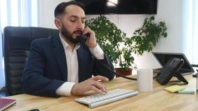 Homem de negócios novo no telefone no escritório filme