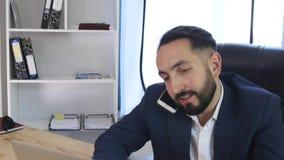 Homem de negócios novo no telefone no escritório video estoque