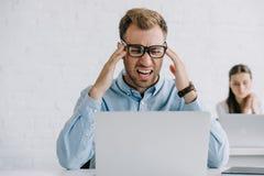 homem de negócios novo nos monóculos que sofrem da dor de cabeça ao trabalhar com portátil foto de stock royalty free