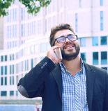 Homem de negócios novo nos vidros com uma barba que fala no telefone que anda abaixo da rua fotografia de stock royalty free