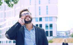 Homem de negócios novo nos vidros com uma barba que fala no telefone que anda abaixo da rua imagem de stock