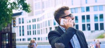 Homem de negócios novo nos vidros com uma barba que fala no telefone que anda abaixo da rua fotos de stock royalty free