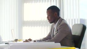 Homem de negócios novo preto que usa o laptop que senta-se em um escritório branco moderno vídeos de arquivo