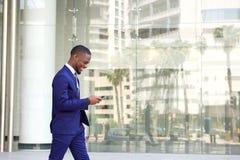Homem de negócios novo que anda e que usa o telefone celular Fotos de Stock Royalty Free
