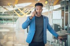 Homem de negócios novo que anda no aeroporto que fala pelo telefone imagem de stock