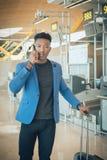 Homem de negócios novo que anda no aeroporto que fala pelo telefone foto de stock royalty free
