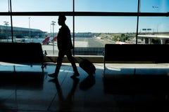 Homem de negócios novo que anda no aeroporto na frente da janela foto de stock